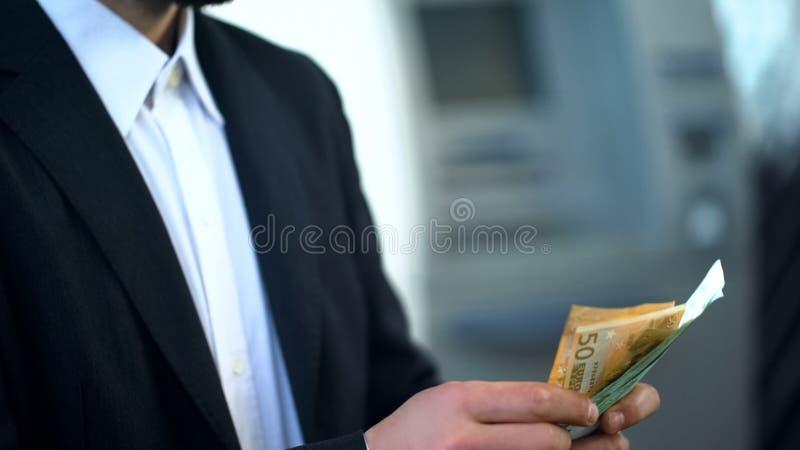 Bemannen Sie die Zählung von Euros in der Bankfiliale, Habenzinsen, rentable Investition stockfotos