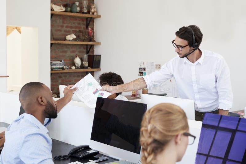 Bemannen Sie Dokument im beschäftigten Bürogroßraum, Abschluss oben führen stockfotos