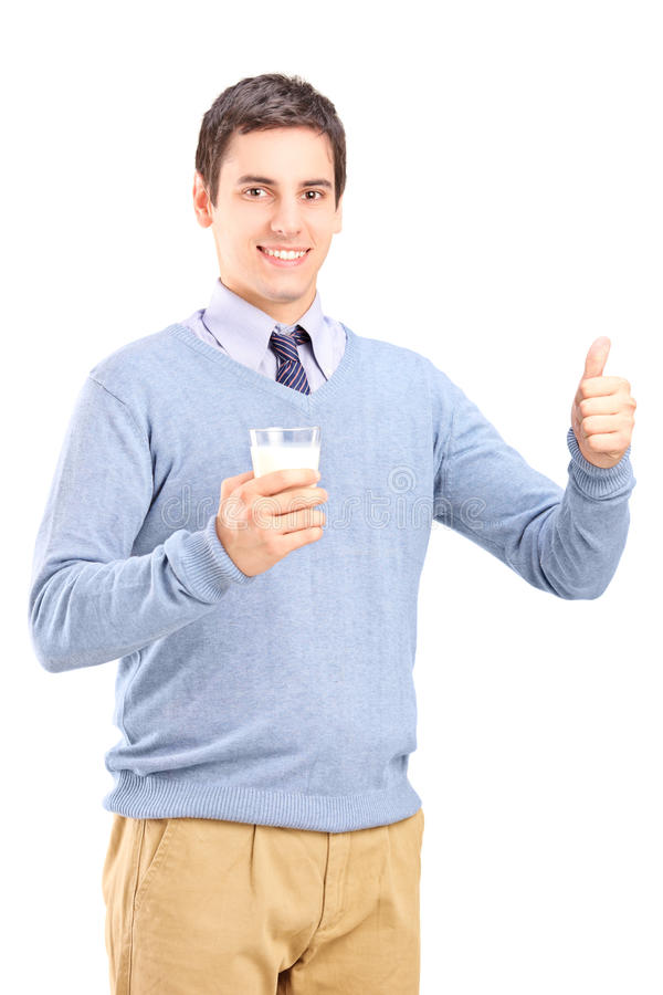 Bemannen Sie ein Glas Milch hochhalten und Daumen geben stockfotografie