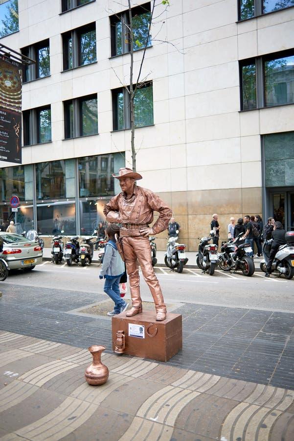 Bemannen Sie eine Skulptur eines Cowboys von einem amerikanischen Westfilm mit Kleidung gemalter Bronzefarbe vollständig simulier lizenzfreies stockbild