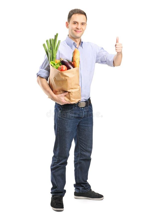 Bemannen Sie eine Tasche von Lebensmittelgeschäften hochhalten und Daumen geben lizenzfreie stockfotos