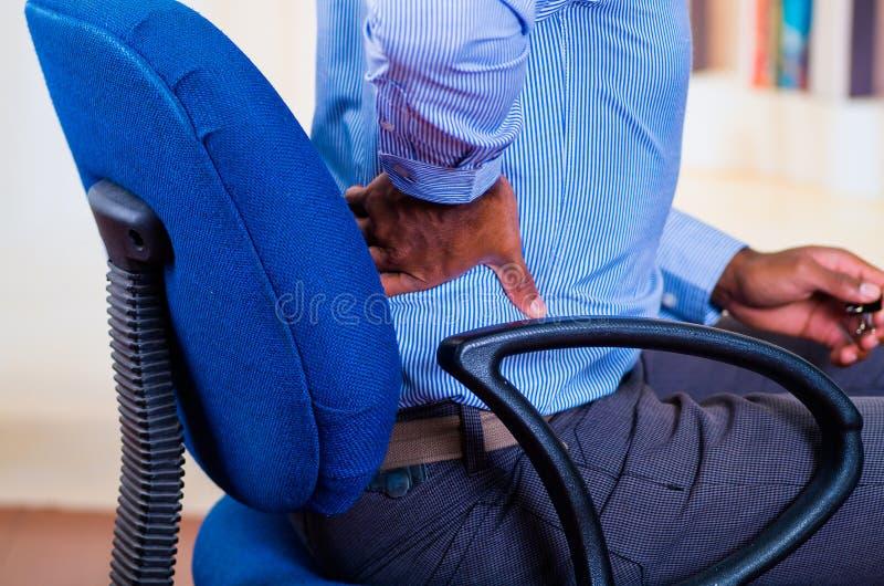 Bemannen Sie in einem Stuhl anscheinend arbeiten, sitzen und seins zurück halten, Schmerzsignal stockbilder
