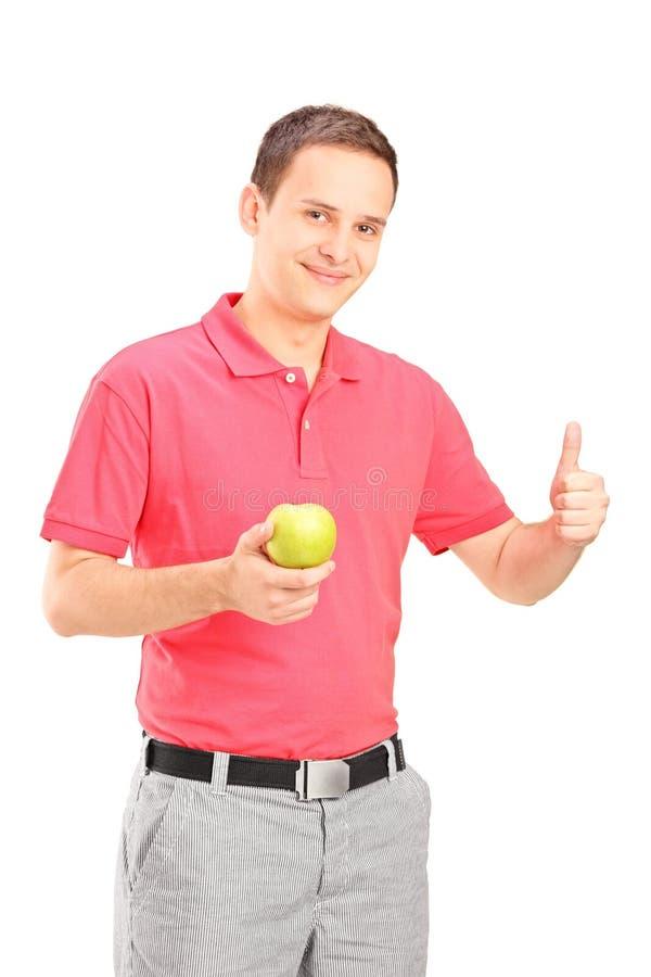Bemannen Sie einen Apfel hochhalten und Daumen geben stockbild