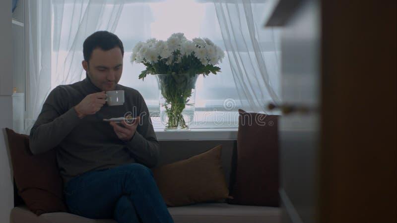 Bemannen Sie einen Kaffee auf Sofa zu Hause trinken und schauen durch Fenster stockfotos