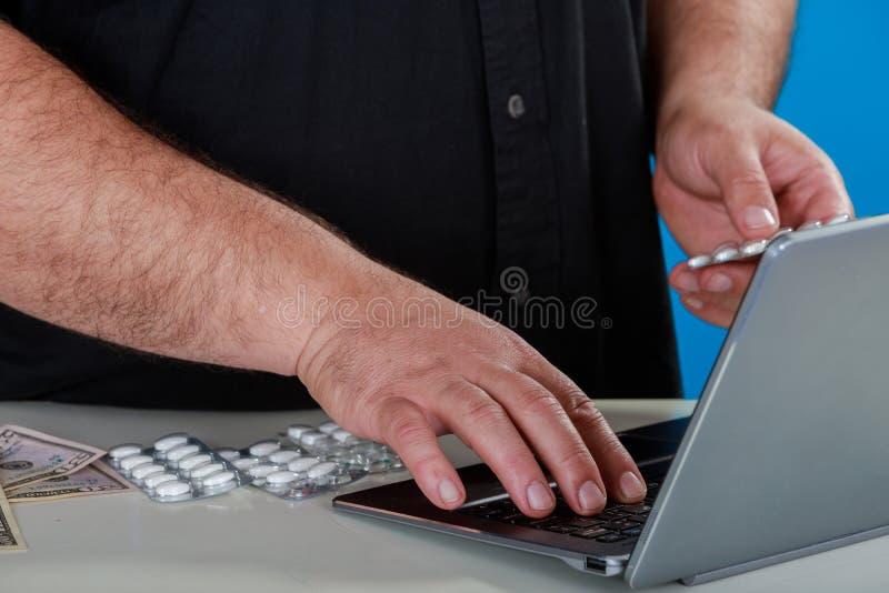 Bemannen Sie Einrichtungsdrogen oder Ergänzungen von einer Internet-Apotheke ein Laptop, der über die Drogen erforscht oder von e stockbilder