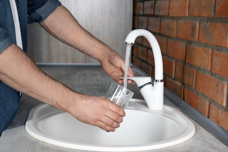 Bemannen Sie füllendes Glas mit Wasser vom Hahn in der Küche stockfotografie