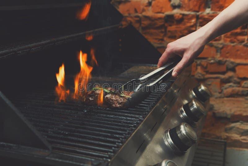 Bemannen Sie Fleischsteaks auf Berufsgrill draußen kochen lizenzfreies stockfoto