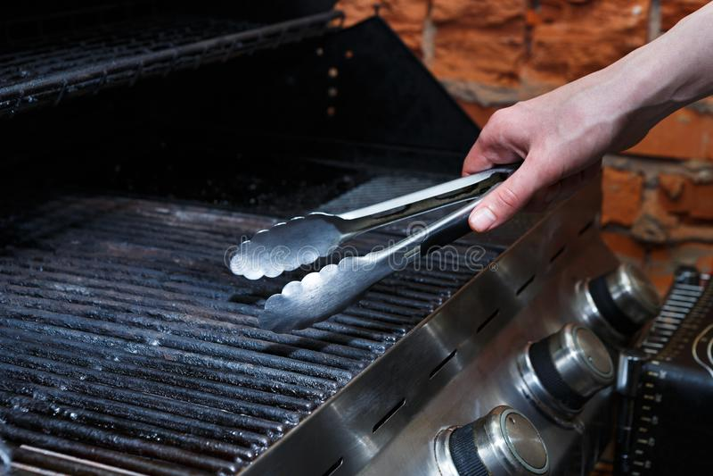 Bemannen Sie Fleischsteaks auf Berufsgrill draußen kochen stockfotografie