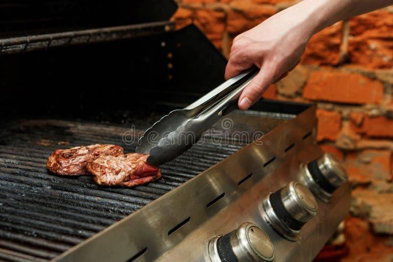 Bemannen Sie Fleischsteaks auf Berufsgrill draußen kochen lizenzfreies stockbild