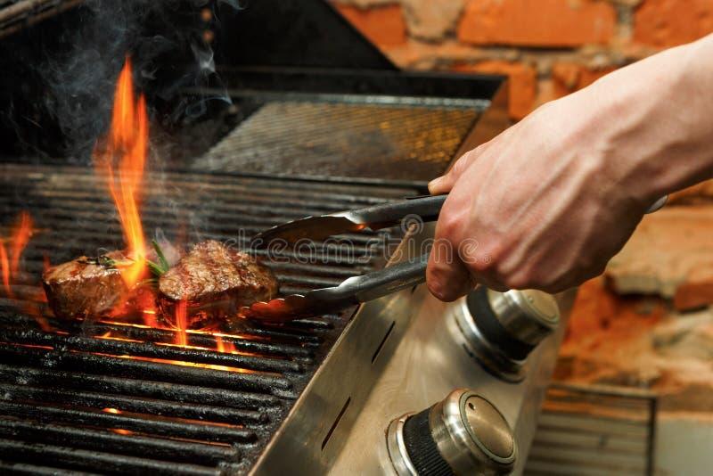 Bemannen Sie Fleischsteaks auf Berufsgrill draußen kochen stockfotos