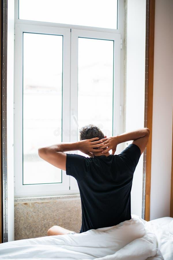 Bemannen Sie glaubenden hinteren Schmerz im Bett, nachdem Sie morgens geschlafen haben stockbild