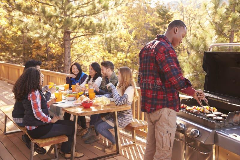 Bemannen Sie Grills für Freunde an einem Tisch, auf einer Plattform in einem Wald stockbild