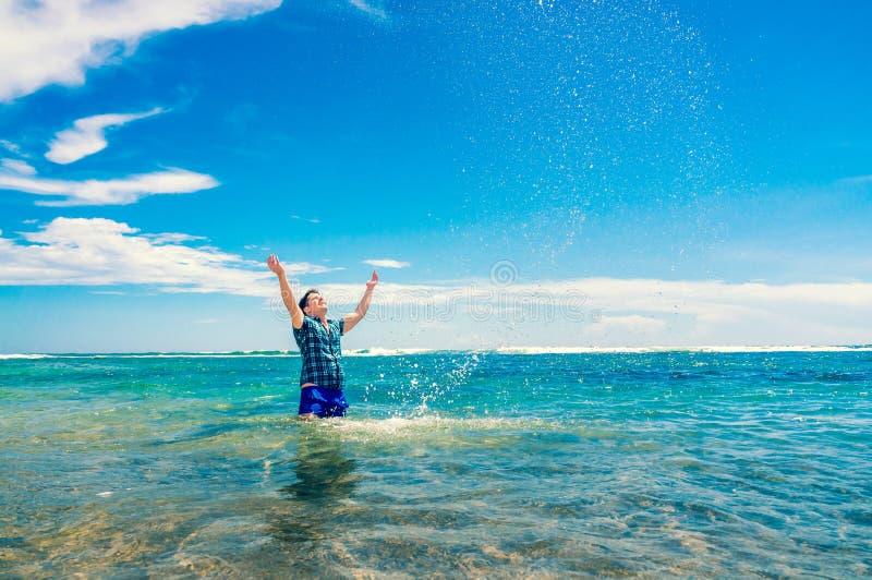 Bemannen Sie Haben des Spaßes im Wasser auf dem Strand lizenzfreie stockfotos
