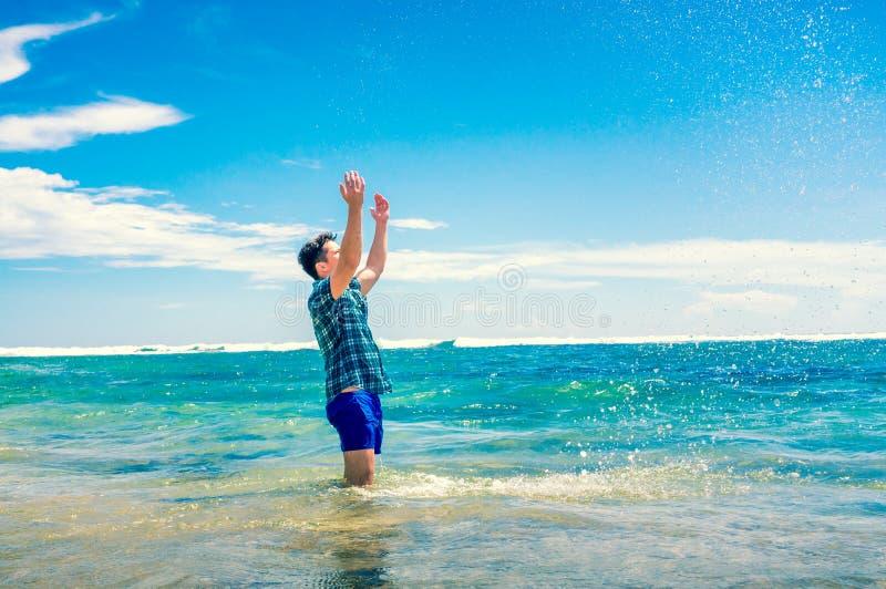 Bemannen Sie Haben des Spaßes im Wasser auf dem Strand stockfoto