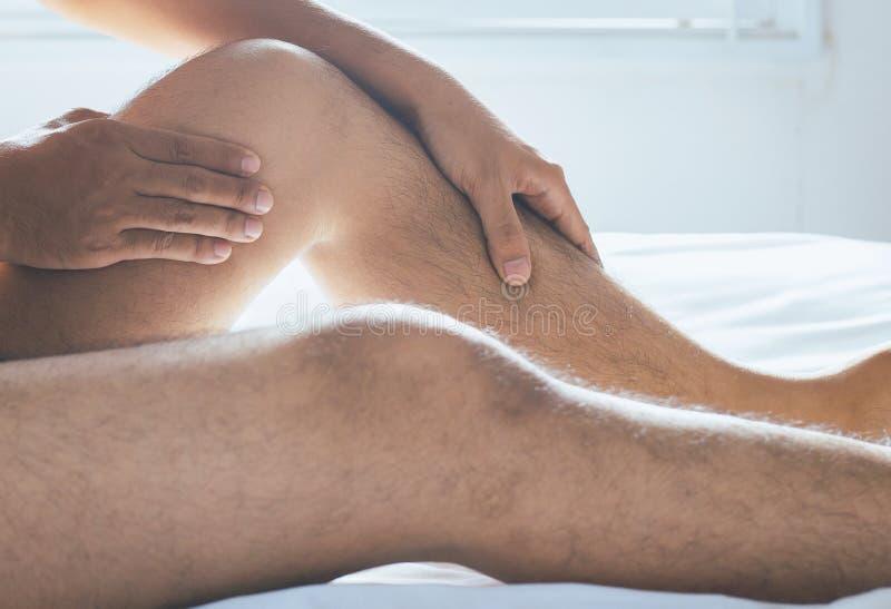 Bemannen Sie Haben eines erschöpften und schmerzlichen Beinschmerzgefühls lizenzfreies stockfoto