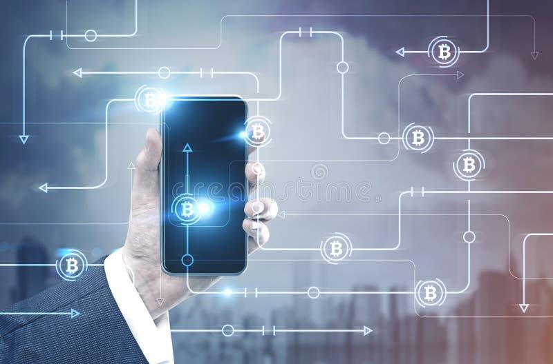 Bemannen Sie Hand mit einem Smartphone, bitcoin Netz, Stadt stockbild