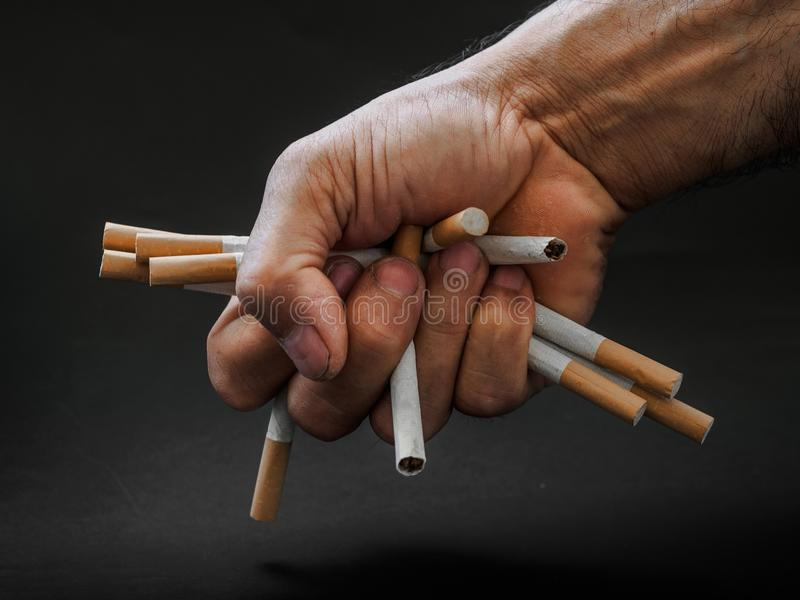 Bemannen Sie Handholding und zerstören Sie Zigaretten auf schwarzem Hintergrund Qui stockbilder