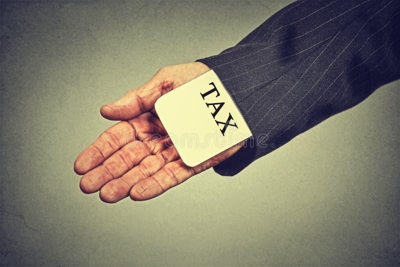 Bemannen Sie Handversteckende Steuerkarte in einem Ärmel einer Klage Steuerhinterziehungswirtschaftskonzept stockbilder