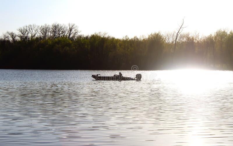 Bemannen Sie heraus in Fischerboot auf Fluss am frühen nebeligen Morgen mit Rauche vom Außenbordmotor, der gegen Bäume darstellt lizenzfreie stockbilder