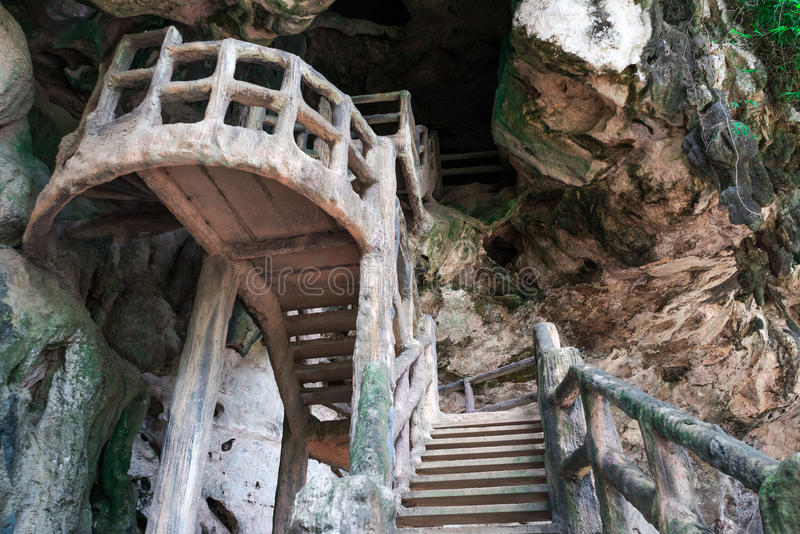 Bemannen Sie hergestellte Treppe bis zur dunklen Höhle auf felsiger Klippe stockfoto
