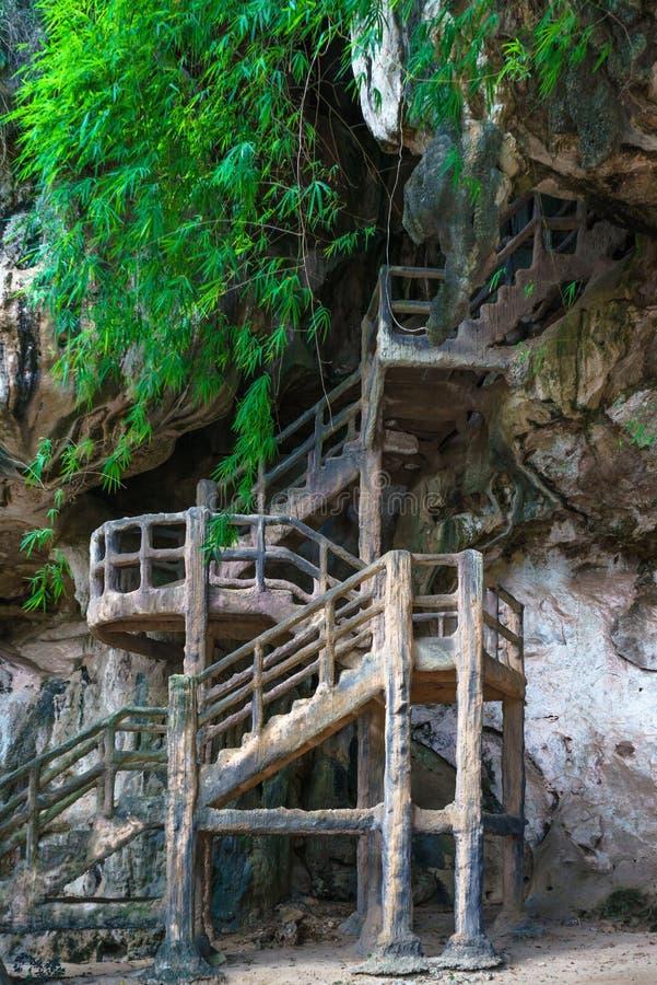 Bemannen Sie hergestellte Treppe in Höhle auf felsiger Klippe stockbild