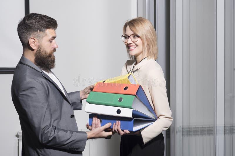 Bemannen Sie Hilfsfrau, um Mappen im Büro zu tragen Geschäftsfrau und Geschäftsmann mit Ordnern Bärtiger Mann und sexy Mädchen mi stockfotos