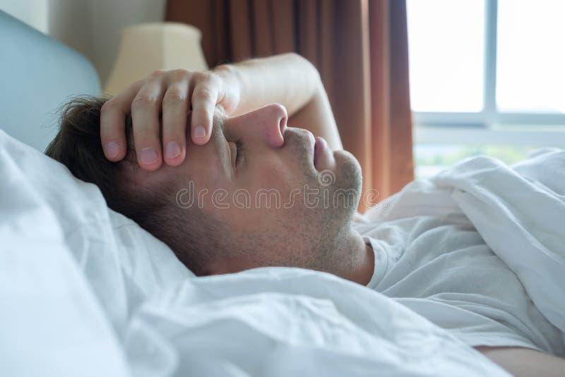 Bemannen Sie im Bett zu Hause liegen, das unter Kopfschmerzen oder Kater leidet lizenzfreie stockfotografie