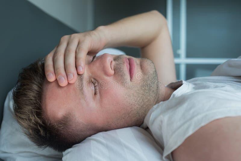 Bemannen Sie im Bett zu Hause liegen, das unter Kopfschmerzen oder Kater leidet stockbilder