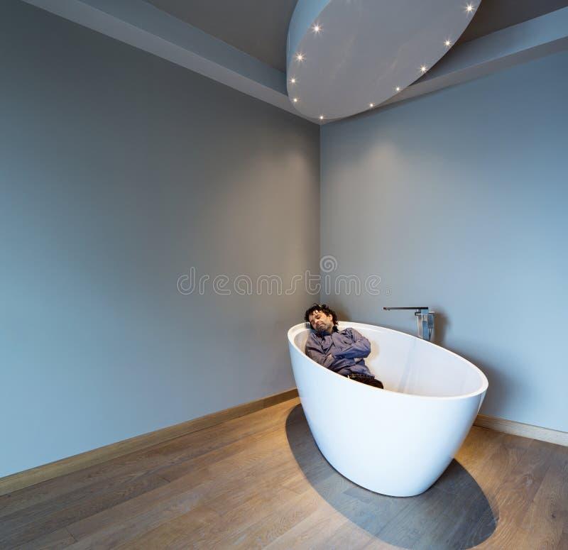 Bemannen Sie innerhalb einer Luxusbadewanne in der modernen Wohnung stockfoto