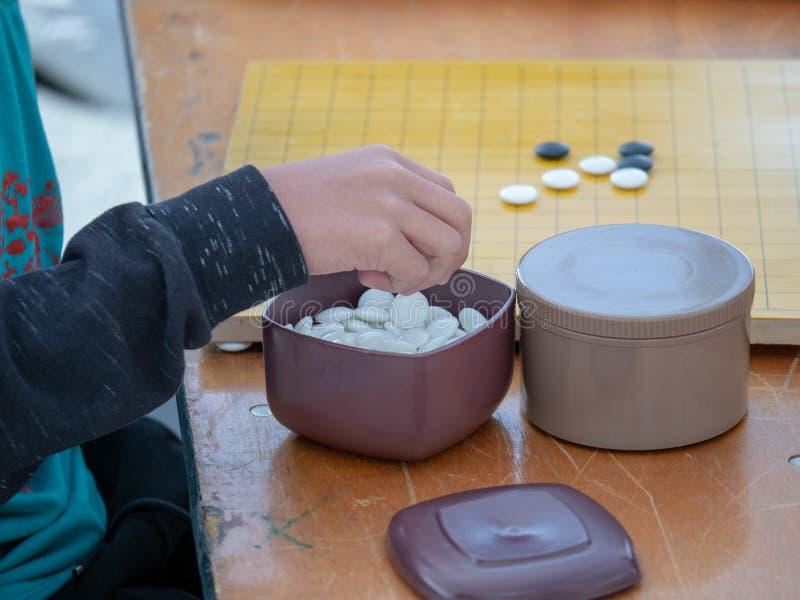Bemannen Sie jonglierende weiße Steine beim Spielen des chinesischen Spiels von Go stockfotos