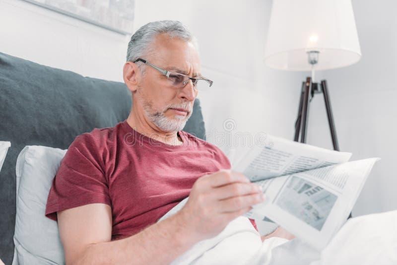 Bemannen Sie Lesezeitung beim im Bett zu Hause liegen lizenzfreie stockbilder