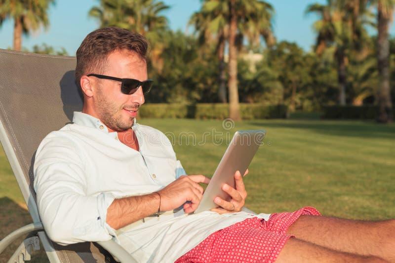 Bemannen Sie Lesung auf seiner Tablette und Touch Screen lizenzfreies stockfoto