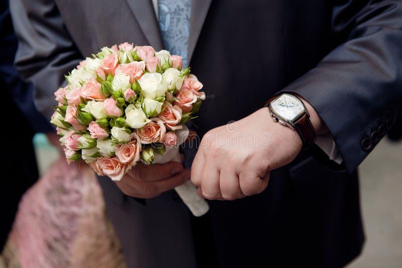 Bemannen Sie mit den Uhrhänden einen Blumenblumenstrauß stockfotos