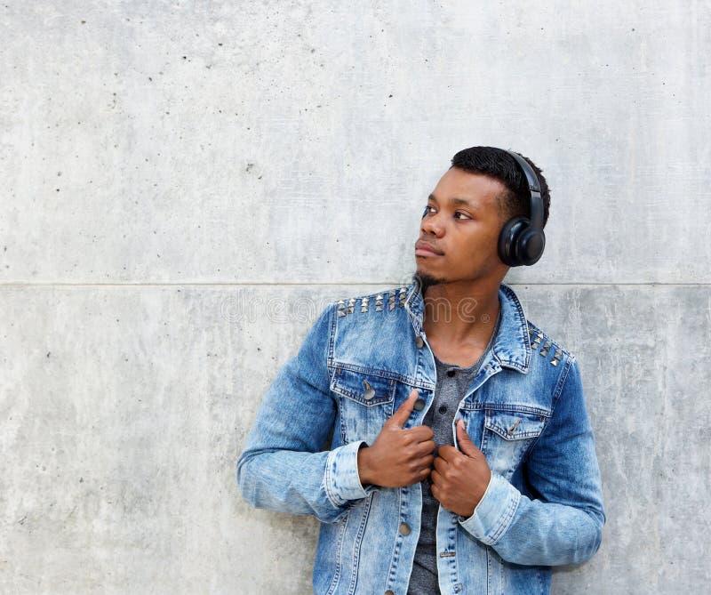 Bemannen Sie mit der Jeansjacke und drahtlosen Kopfhörern, die weg schauen lizenzfreies stockbild
