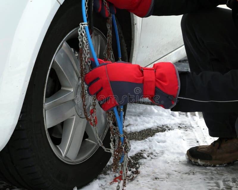 Bemannen Sie Montageschneeketten im Autoreifen im Winter lizenzfreies stockbild