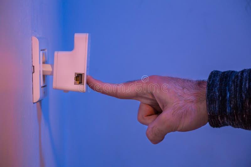 Bemannen Sie Presse mit seinem Finger auf WPS-Knopf auf WiFi-Verstärker, das i lizenzfreies stockbild