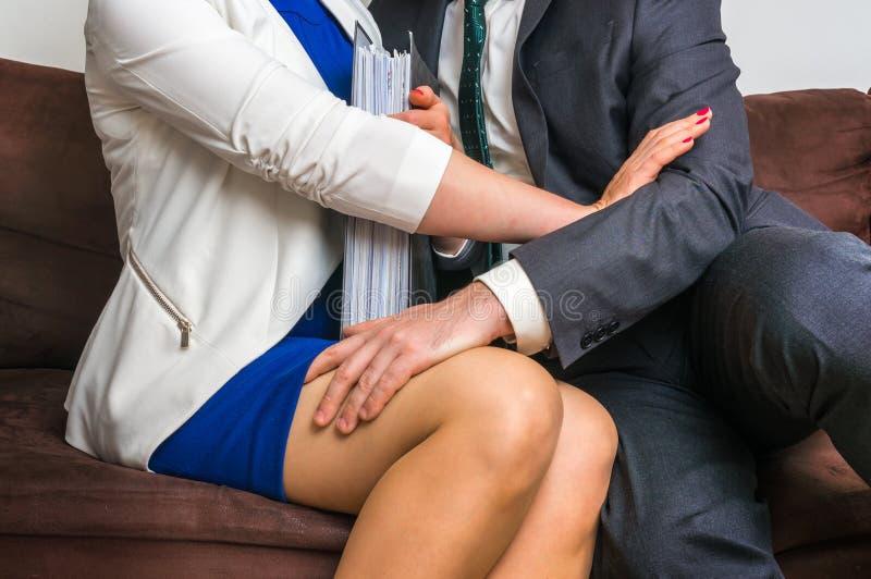 Bemannen Sie rührendes Frau ` s Knie - sexuelle Belästigung im Büro lizenzfreie stockfotografie