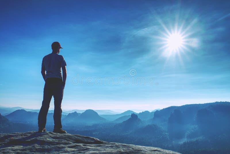 Bemannen Sie am Rand einer Klippe über nebelhaftem Tal hoch gehen Reise-Wandern und Lebensstil  lizenzfreie stockbilder