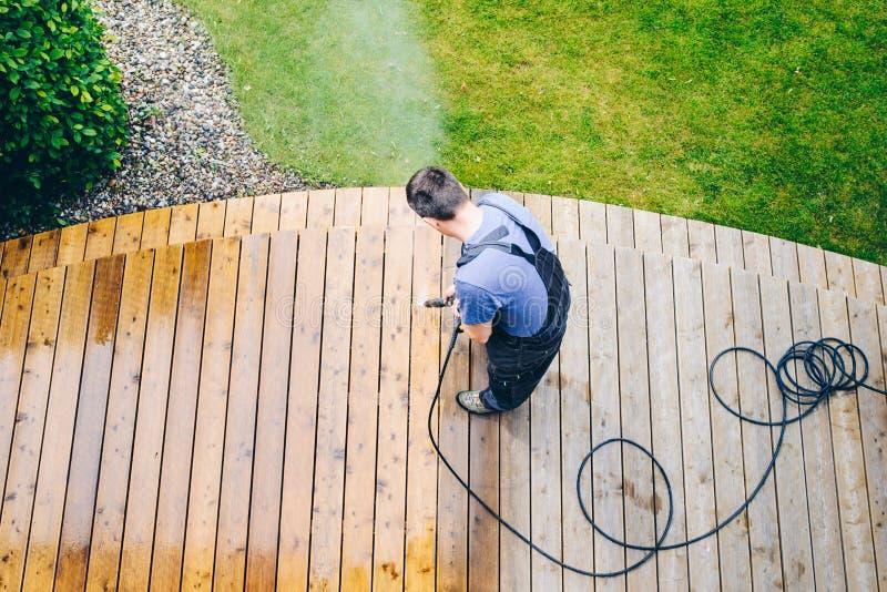 bemannen Sie Reinigungsterrasse mit einer Energiewaschmaschine - Hochwasserdruck c lizenzfreie stockfotos