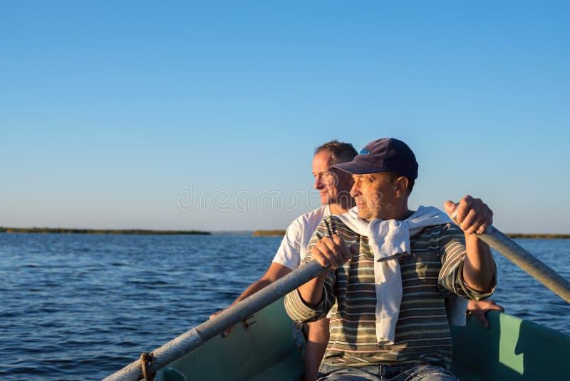 Bemannen Sie Rudersport auf einem Boot auf dem Meer stockfoto