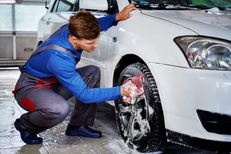 Bemannen Sie ` s Auto der Arbeitskraft waschende Leichtmetallfelgen auf einer Waschanlage lizenzfreie stockfotos
