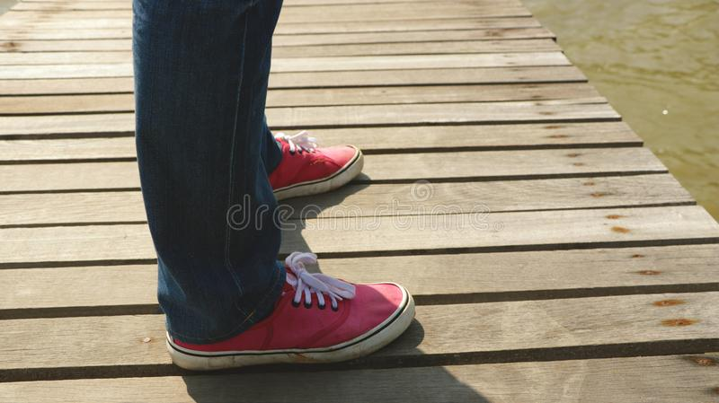 Bemannen Sie ` s Beine, die Jeans und rote Gewebe-Schuhe auf hölzernem Dock tragen - stehend im Sun lizenzfreie stockbilder