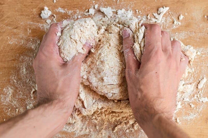 Bemannen Sie ` s Hände, die den Teig machen und Brot zubereiten, Pizza auf braunem hölzernem Hintergrund Garprozess - Mann kneten lizenzfreie stockfotografie