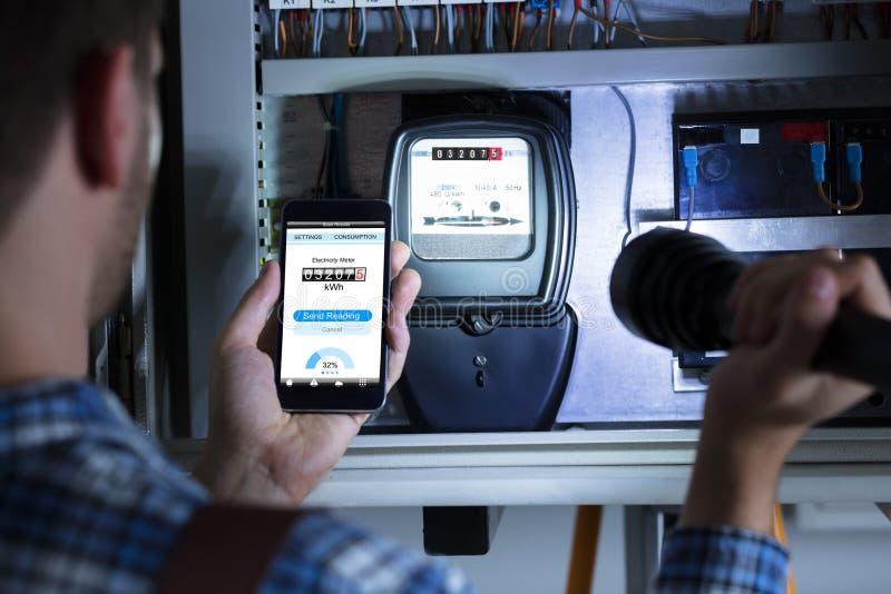 Bemannen Sie ` s Hand, die den Handy hält, der Stromzähler-Lesung zeigt lizenzfreie stockbilder