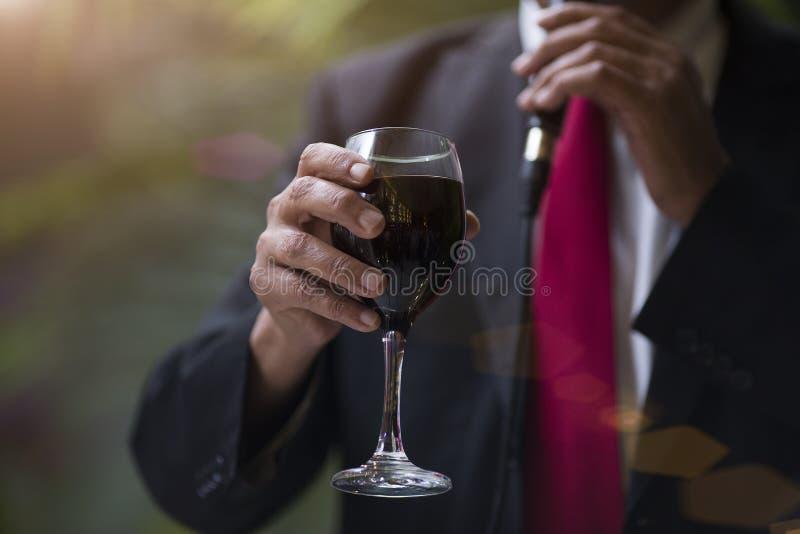 Bemannen Sie ` s Hand mit einem Glas Rotwein lizenzfreie stockfotos