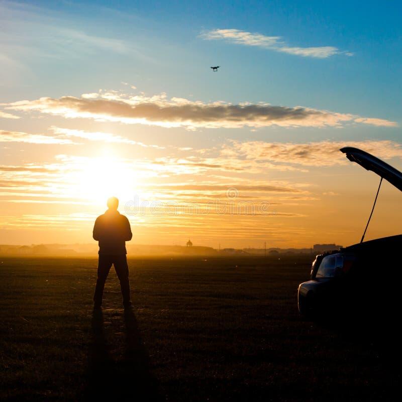 Bemannen Sie Schattenbild mit rc flacher Stellung auf Sonnenuntergang stockfoto