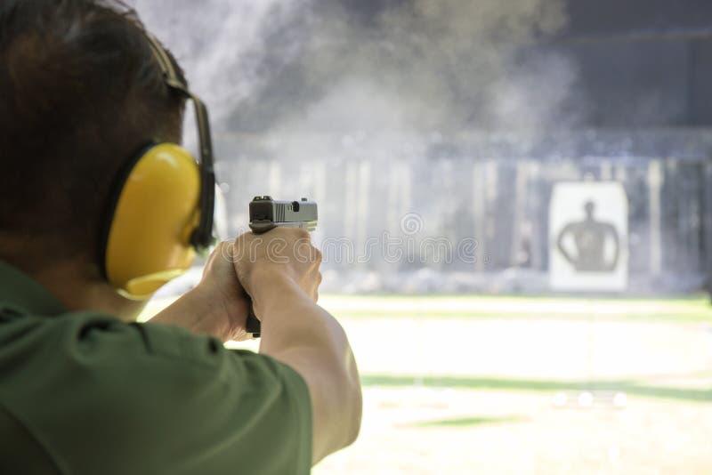 Bemannen Sie schießende automatische Pistole, um im Schießstand anzuvisieren stockbild