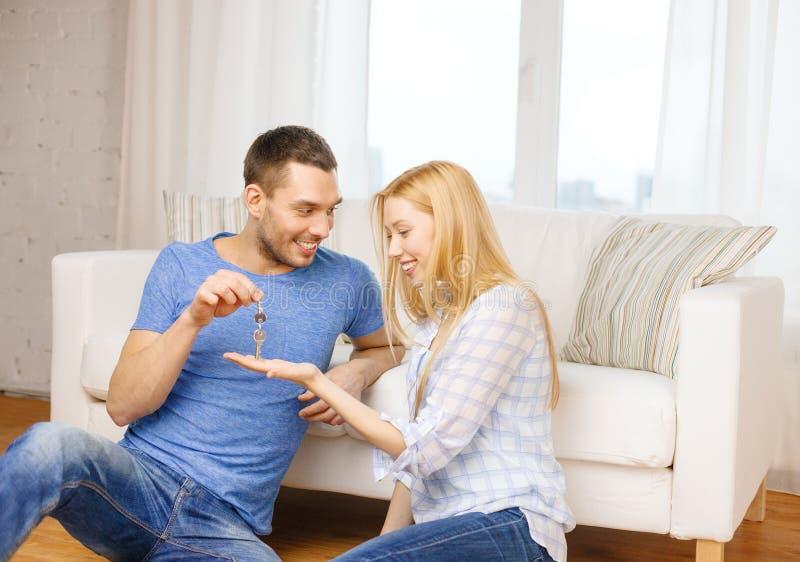 Bemannen Sie Schlüssel zu Hause geben der Freundin oder der Frau lizenzfreie stockfotografie