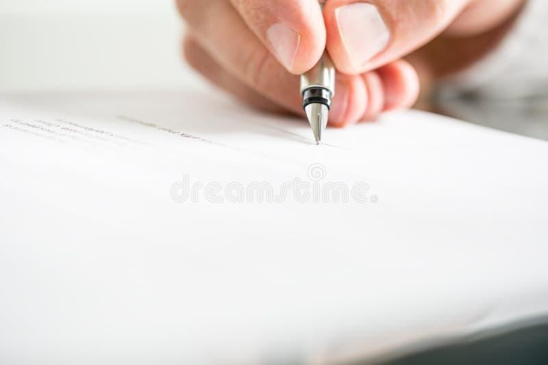 Bemannen Sie Schreiben auf einem Dokument mit einem Füllfederhalter stockbild