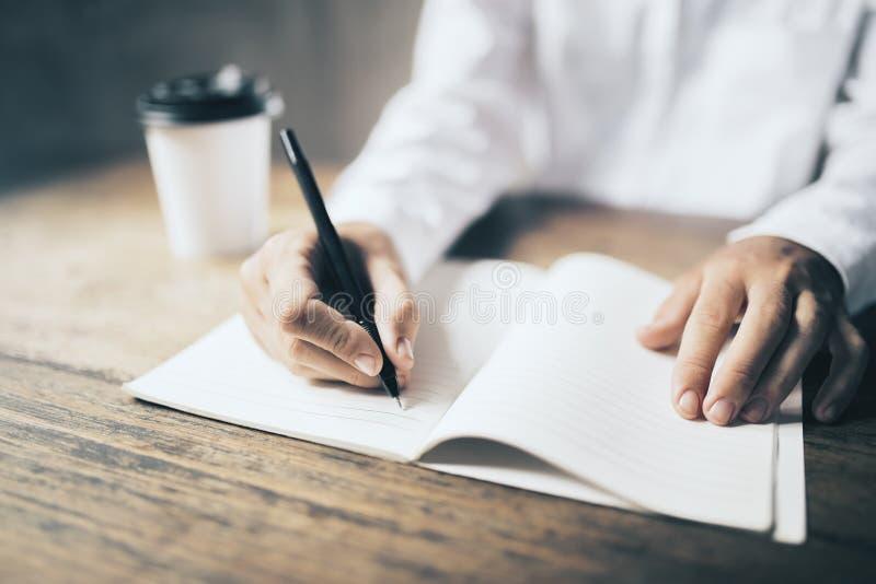 Bemannen Sie Schreiben im leeren Tagebuch und in der Papierkaffeetasse auf Holztisch stockfoto